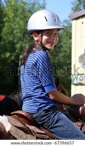 a young girl horseback riding - stock photo