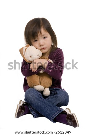 A young girl hugs here bunny as she cries. - stock photo
