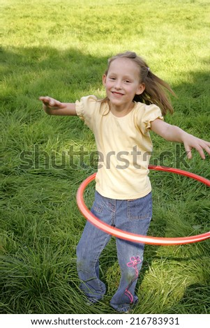 A young girl hula hooping.