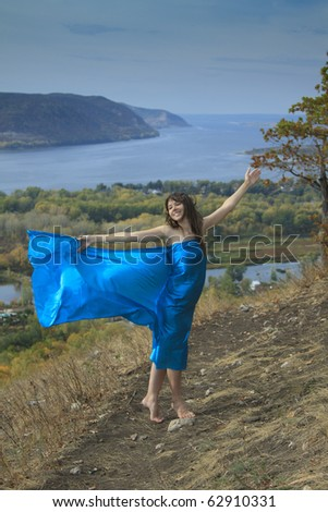 A young girl in a blue dress dancing on a mountaintop. Young woman with blue fabric fluttering on wind .