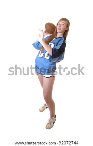A young girl in a blue football outfit standing in the studio and show how to play football, for white background. - stock photo