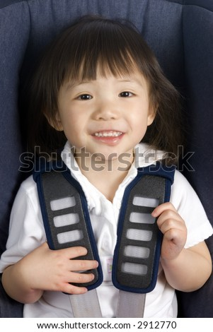 A young girl in a car seat for safety. - stock photo