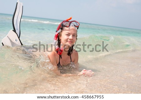 A young girl in a mask for swimming with flippers lying on the beach and smiling