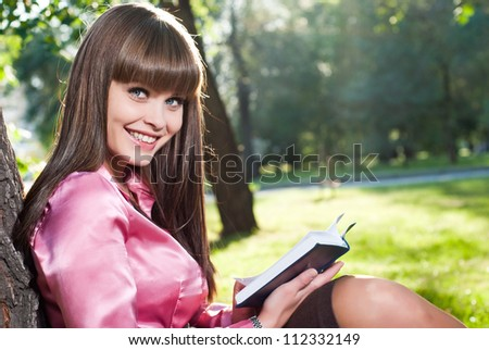 A young girl in a park, reading a book - stock photo