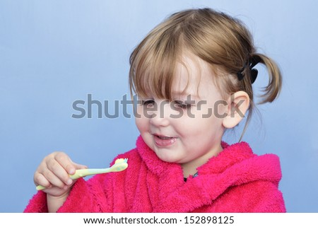 A young girl in a pink dressing gown against a light blue background. She's cleaning her teeth and has stopped to smile at the brush. - stock photo