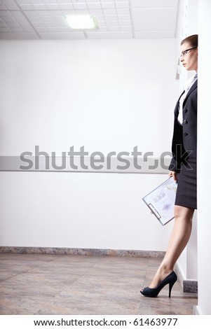 A young girl in a serious suit goes out the door - stock photo