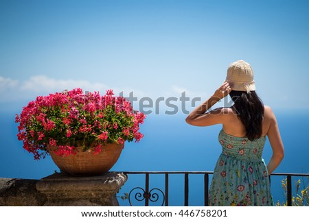 A young girl in a sun-hat near blossom flowers staying at the sea coast and looking forward to the horizon - stock photo