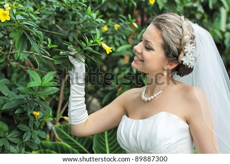 A young girl in a white wedding dress is considering a flower on a tree limb and smiles - stock photo