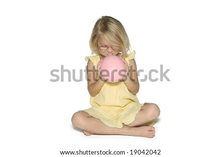 A young girl in a yellow dress sitting down and blowing up a pink balloon.  Isolated on a white background