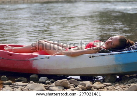A young girl in bikini lying on the boat and sunbathing near the river, enjoying holidays in Laos - stock photo
