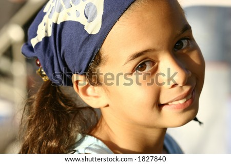 A young girl in blue bandanna enjoying the evening sun - stock photo