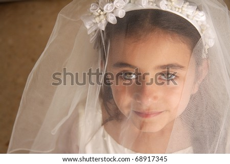 A young girl in her holy communion outfit looking at the camera from behind her veil. Stunning green eyes - stock photo