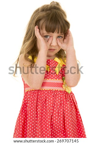 a young girl in her polka dot dress with her hands up by her face. - stock photo