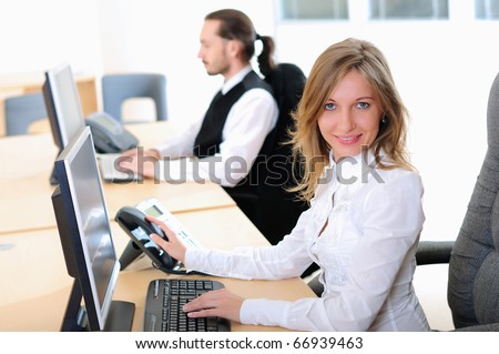 A young girl in his office at his workplace works at the computer