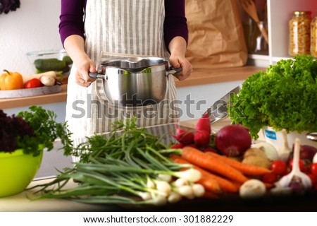 A young girl in kitchen while cooking - stock photo