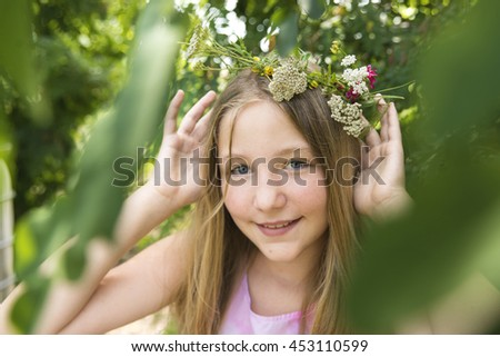 A young girl in the orchard with garlands on their heads. - stock photo