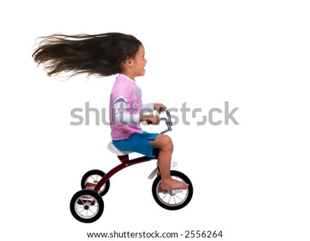 A young girl is cruising on her tricycle.... speed demon - stock photo