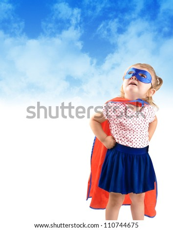 A young girl is dressed up as a superhero and looking up in the sky with a mask and cape. There is a copyspace to add a message area. Use it for a strength or halloween concept. - stock photo