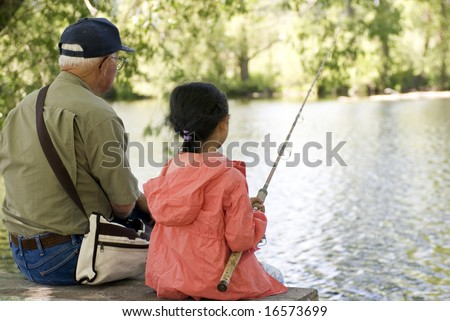 A young girl is fishing with her grandpa on a warm summer day. - stock photo