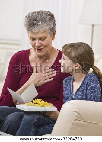 A young girl is handing a present to her grandmother, who is reading the card.  They are smiling and looking away from the camera.  Vertically framed shot. - stock photo