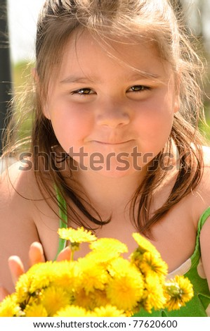 A young girl is holding a bouquet of dandelions.