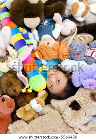 A young girl is in the middle of a big pile of stuffed animals. - stock photo