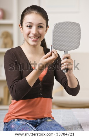 A young girl is looking into a handheld mirror and putting makeup on.  She is smiling at the camera.  Vertically framed shot. - stock photo