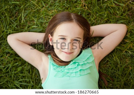 A young girl is lying on her back on the green grass smiling.