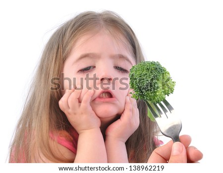 A young girl is making a funny disgusting face at a fork with a healthy piece of broccoli on a white background. - stock photo