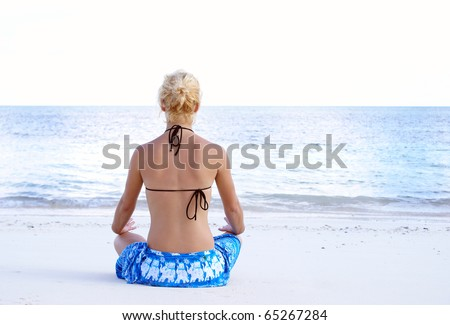 A young girl is meditating on the beach. - stock photo