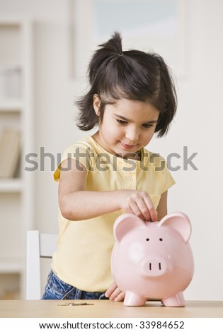A young girl is playing with a piggy bank.  She is looking away from the camera.  Vertically framed shot. - stock photo