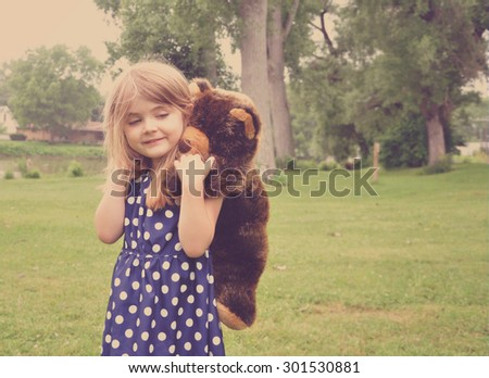 A young girl is playing with a stuffed animal teddy bear on her back outside for a friendship or love concept. - stock photo