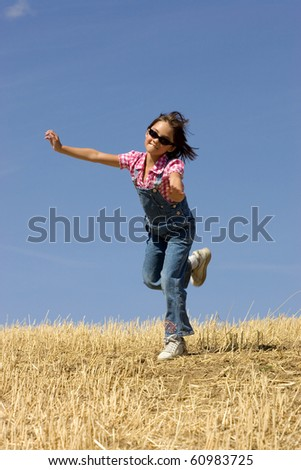 A young girl is prancing around in an already harvested wheat field. - stock photo