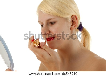 A young girl is putting lipstick on