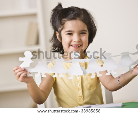 A young girl is seated at a desk and is holding up paper dolls.  She is smiling at the camera.  Horizontally framed shot. - stock photo