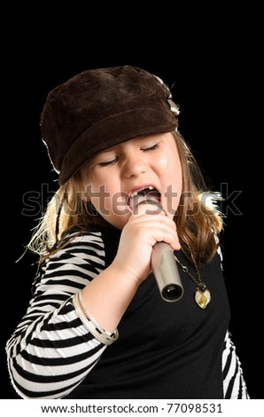 A young girl is singing like a pop star, isolated against a black background. - stock photo