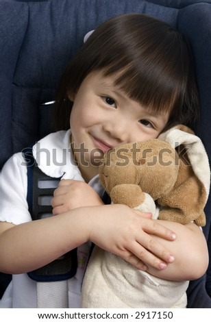 A young girl is strapped into a car seat for safety and holds her bunny. - stock photo
