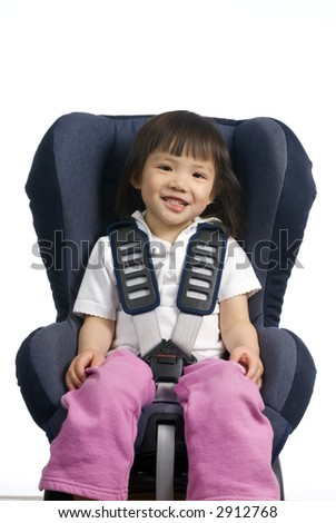 A young girl is strapped into a car seat. Safety and security. isolated on white - stock photo