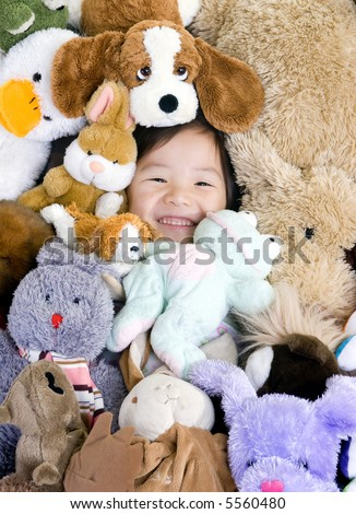 A young girl is surrounded by her stuffed animals. - stock photo