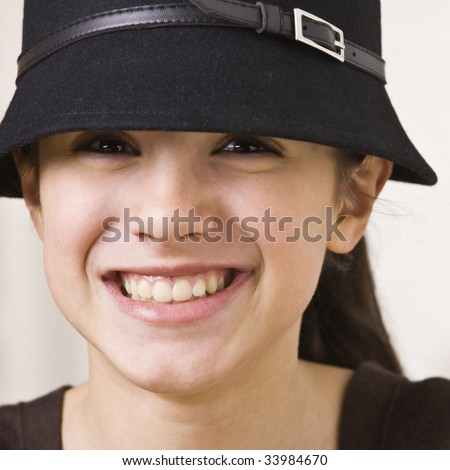 A young girl is wearing a hat and smiling at the camera.  Square composition. - stock photo