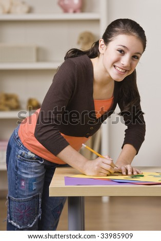 A young girl is working on a project and smiling at the camera.  Vertically framed shot. - stock photo