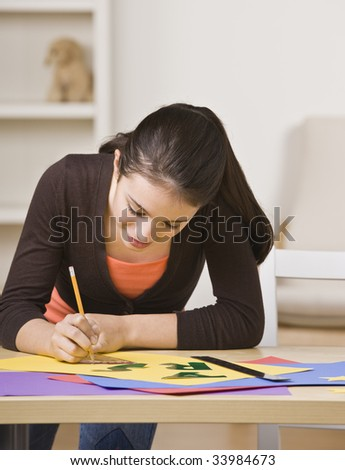 A young girl is working on a project.  She is smiling and looking down at her work.  Square framed shot. - stock photo