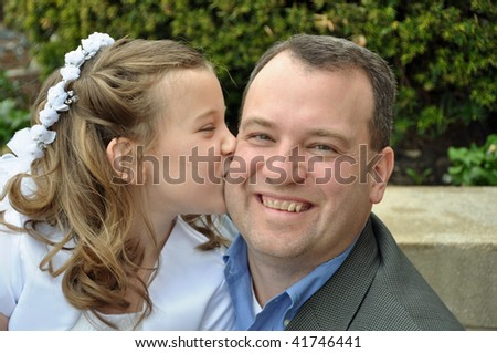 a young girl kisses her father on her first communion day - stock photo