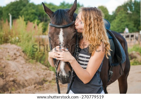 a young girl kisses the brown horse in the face