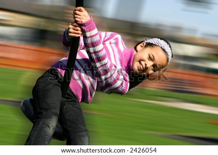 A young girl laughing happily as she rides on the playground pole on a warm day. - stock photo