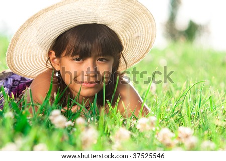 a young girl lays in the grass with a big straw hat on - stock photo