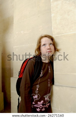 A young girl leans against a stone wall looking up and away from the camera. - stock photo