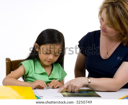 A young girl learns to write with the help of a teacher. - stock photo