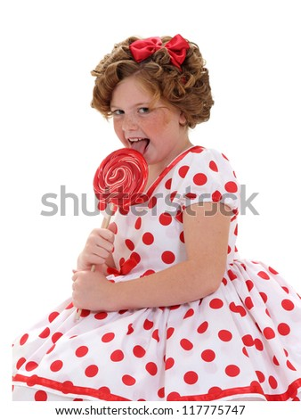 A young girl licks a red lollipop isolated on white