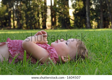 A young girl lies down in the grass and rests her hands on her chest after a long afternoon of playing at the park.